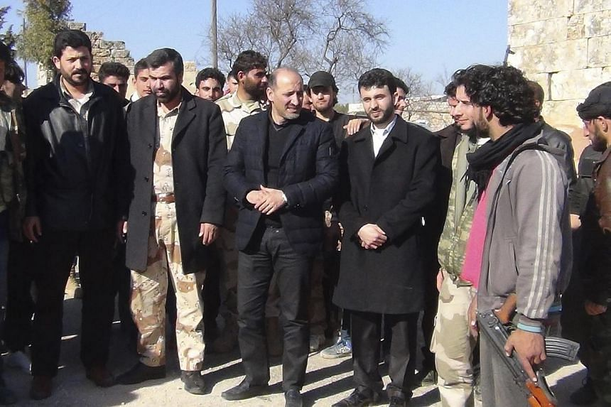 Syrian opposition leader Ahmad Jarba (Center) visits leaders in the Free Syrian Army in Idlib province February 14, 2014.Syrian opposition leader Ahmad Jarba will lead a delegation to China this week and meet the country's foreign minister, the