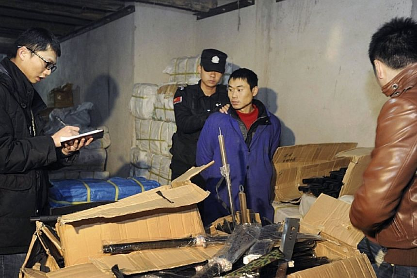 Police holds a suspect as they count replica guns in Shaodong, Hunan province on March 1, 2014. -- PHOTO: REUTERS