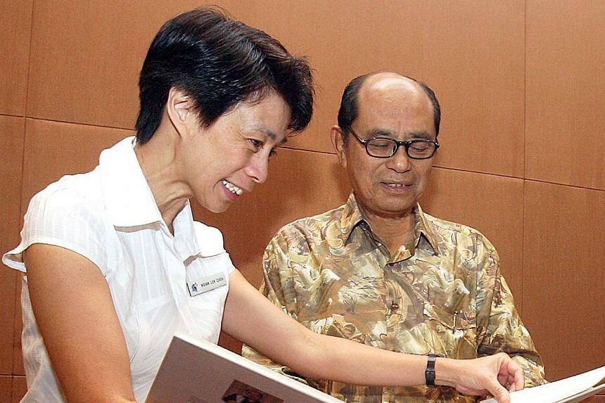 Abdul Ghani Abdul Hamid with the National Library Board's Ngian Lek Choh looking at one of his books to be preserved and archived at the library in September 2007. PHOTO: BH FILE