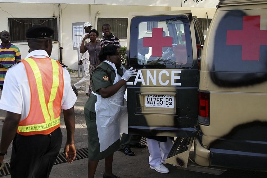 A military nurse helps victims of a bomb blast off an ambulance at the Asokoro General Hospital in Abuja on April 14, 2014. -- PHOTO: REUTERS