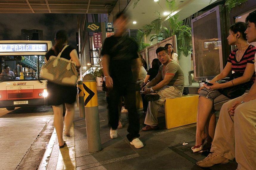 Passengers waiting for night riders at a bus-stop outside Clarke Quay MRT on June 15, 2008.SMRT will end its seven Night Rider services more than two hours earlier from April 30 and run them only one-way from the city. -- ST FILE PHOTO:NG