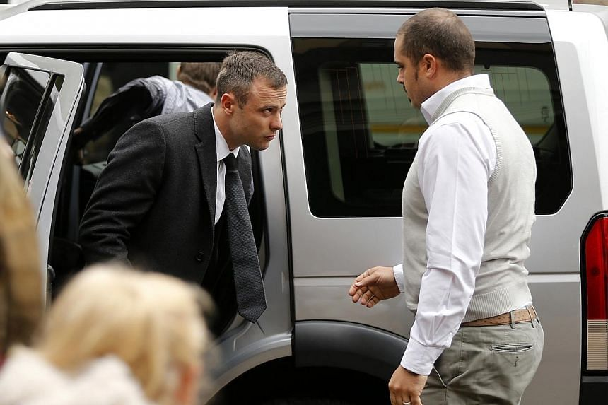 Olympic and Paralympic track star Oscar Pistorius (left) arrives ahead of his trial for the murder of his girlfriend Reeva Steenkamp at the North Gauteng High Court in Pretoria on April 14, 2014. Oscar Pistorius argued with his girlfriend shortl