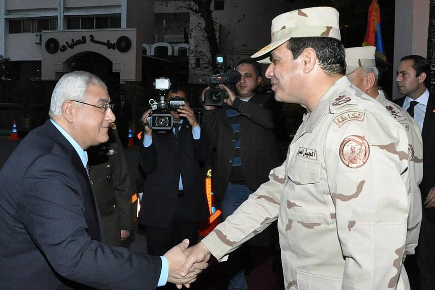 Egypt's interim President Adly Mansour (left) shakes hands with Egypt's army chief Field Marshal Abdel Fattah al-Sisi (right), after his meeting with members of the Supreme Council of the Armed Forces, in Cairo on March 26, 2014.Egypt's ex-army