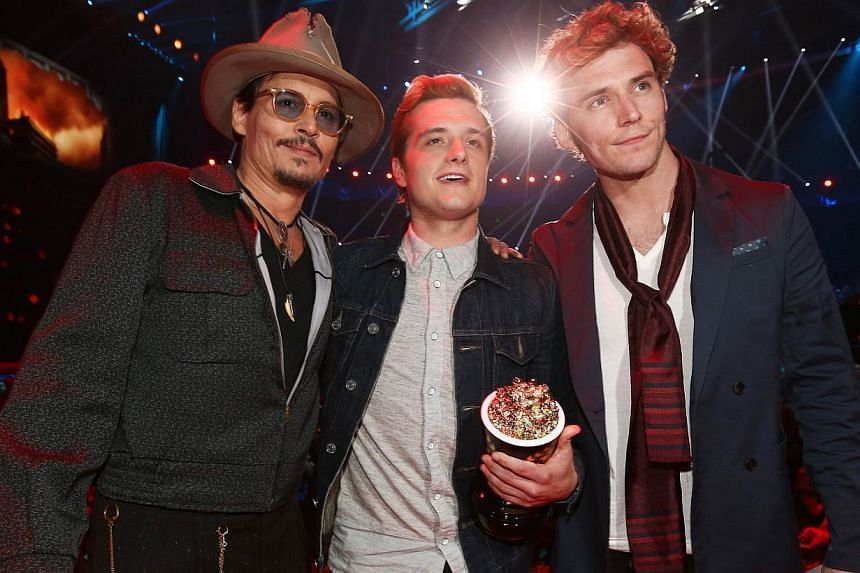 (From left) Actor Johnny Depp poses with actors Josh Hutcherson and Sam Claflin, winners of the Movie of the Year award for The Hunger Games: Catching Fire, at the 2014 MTV Movie Awards at Nokia Theatre Live in Los Angeles, California, on April 13, 2