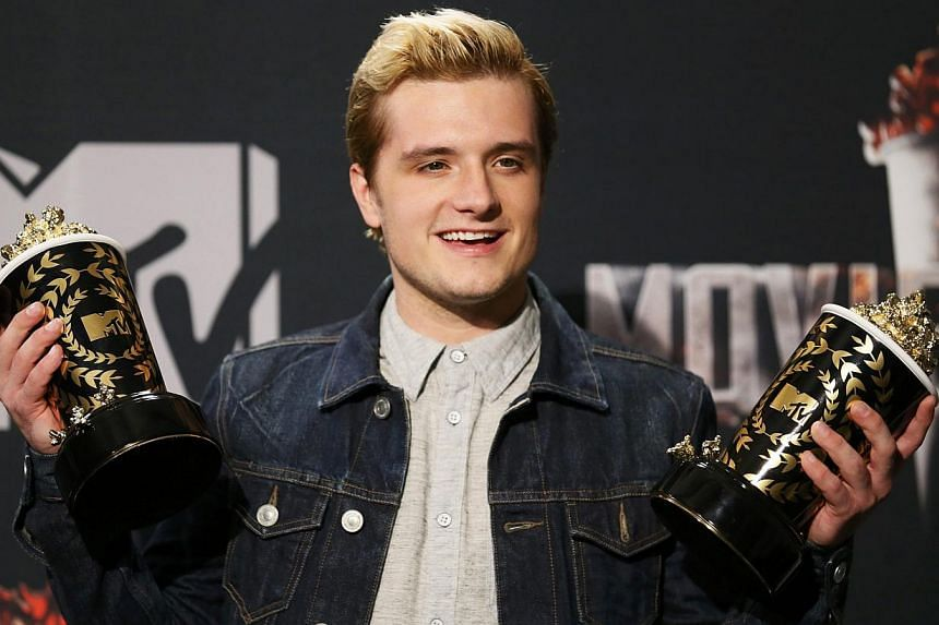 Actor Josh Hutcherson poses backstage with his awards for Best Male Performance and Best Movie of the Year for his performance in The Hunger Games: Catching Fire at the 2014 MTV Movie Awards in Los Angeles, California, on April 13, 2014. -- PHOTO: RE