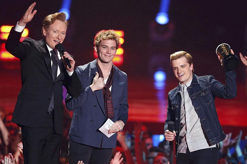 """Host Conan O'Brien (left) closes the show after Sam Claflin (centre) and Josh Hutcherson accepted the award for Best Movie of the Year for """"The Hunger Games: Catching Fire"""" at the 2014 MTV Movie Awards in Los Angeles, California April 13, 2014."""
