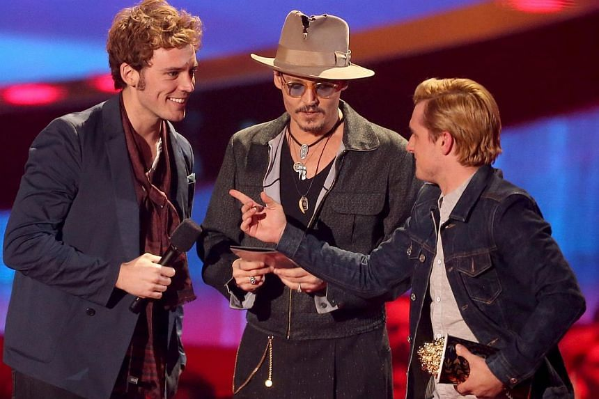 Actors Sam Claflin (left) and Josh Hutcherson accept the Movie of the Year award for The Hunger Games: Catching Fire from actor Johnny Depp (centre) onstage at the 2014 MTV Movie Awards at Nokia Theatre Live in Los Angeles, California, on April 13, 2