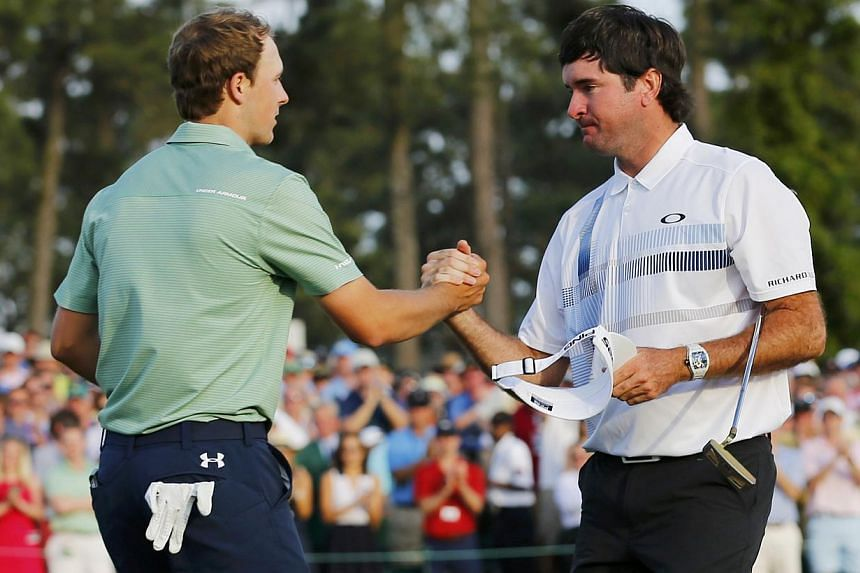 United States golfer Bubba Watson (right) shakes hands with compatriot Jordan Spieth after winning the tournament on the 18th green during the final round of the Masters golf tournament at the Augusta National Golf Club in Augusta, Georgia, on April