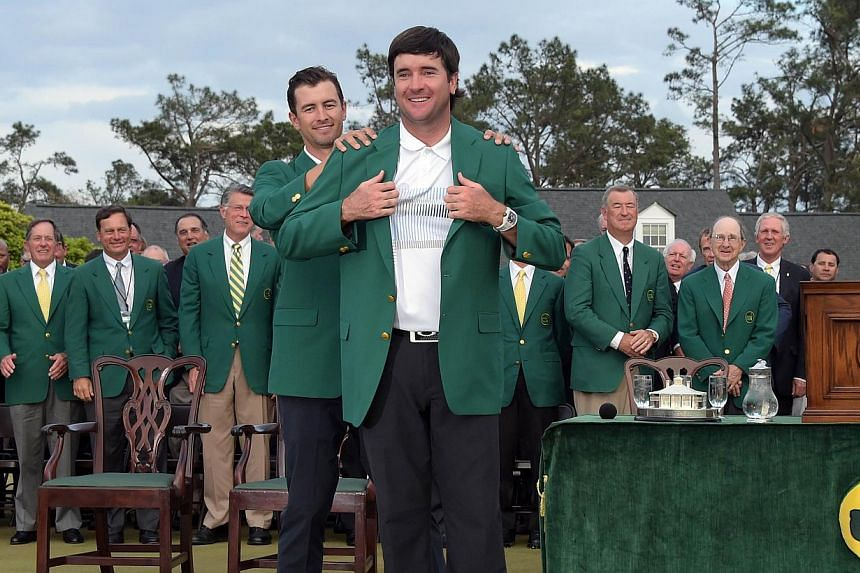 Adam Scott of Australia presents Bubba Watson of the United States a Green Jacket during a ceremony at the end of the 78th Masters Golf Tournament at Augusta National Golf Club in Augusta, Georgia, on April 13, 2014. -- PHOTO: AFP