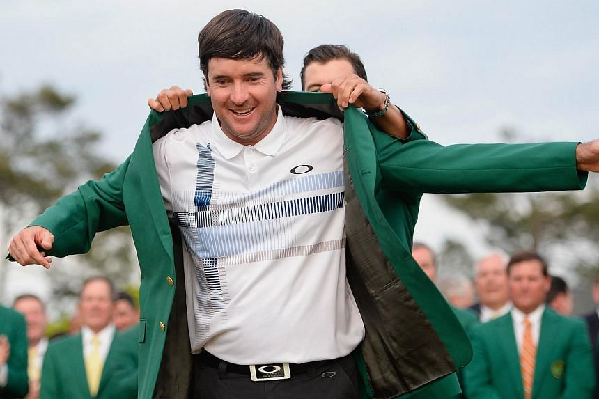 Adam Scott of Australia presents Bubba Watson of the United States with the green jacket after Watson won the 2014 Masters Tournament by a three-stroke margin at Augusta National Golf Club in Augusta, Georgia, on April 13, 2014. -- PHOTO: AFP