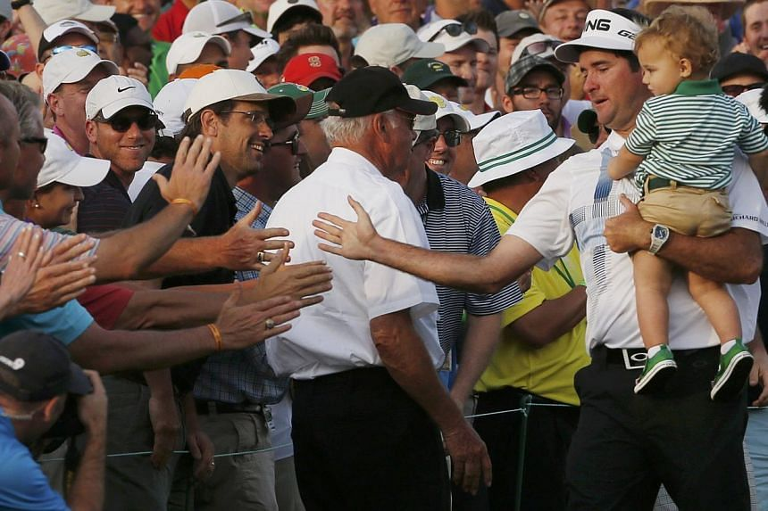 United States golfer Bubba Watson carries his son Caleb and slaps hands with patrons after winning the Masters golf tournament at the Augusta National Golf Club in Augusta, Georgia, on April 13, 2014. -- PHOTO: REUTERS