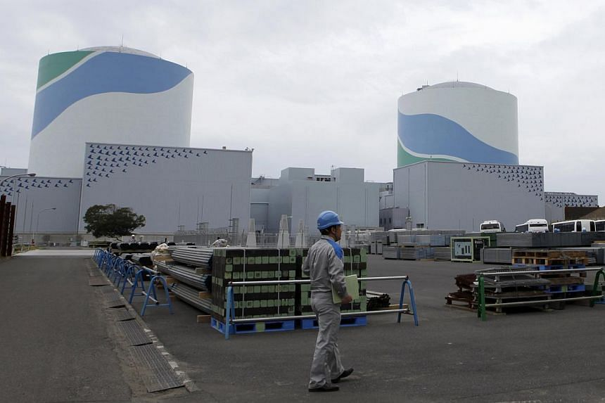 An employee of Kyushu Electric Power Co walks in front of reactor buildings at the company's Sendai nuclear power plant in Satsumasendai, Kagoshima prefecture, on April 3, 2014. -- FILE PHOTO: REUTERS