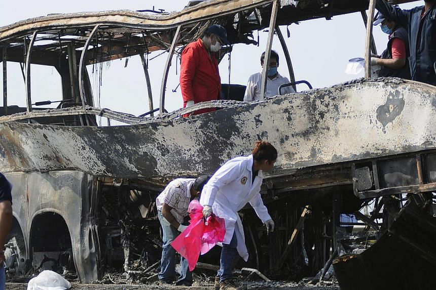 Forensic staff inspect a burnt bus at the scene of an accident on a highway near Juan Rodriguez Clara town, Veracruz state in eastern Mexico, on April 13, 2014. At least 36 people were killed and four were injured in the crash. -- PHOTO: REUTERS