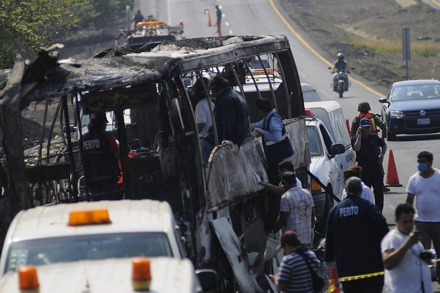 Forensic staff and Red Cross members inspect a bus after a crash on a highway near Juan Rodriguez Clara town, Veracruz state in eastern Mexico, on April 13, 2014. At least 36 people were killed and four were injured in the crash. -- PHOTO: REUTERS