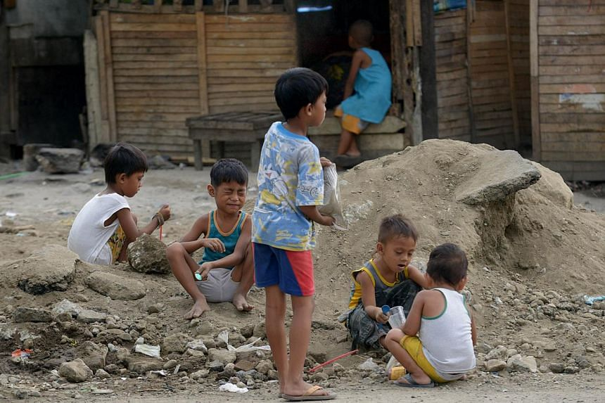 Children play in a slum area in Manila, on April 8, 2014. The Philippines on Monday, April 14, 2014, announced plans to spend more on infrastructure and introduce other reforms to try to lift millions out of poverty.-- FILE PHOTO: AFP