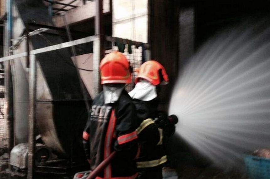 """SCDF firefighters conducting """"damping down"""" operations at Heng Guan Poultry Industries on Monday, April 14, 2014, after extinguishing the blaze.A fire broke out at an abattoir at 32 Senoko Crescent on Monday afternoon.-- PHOTO: SINGAPORE"""