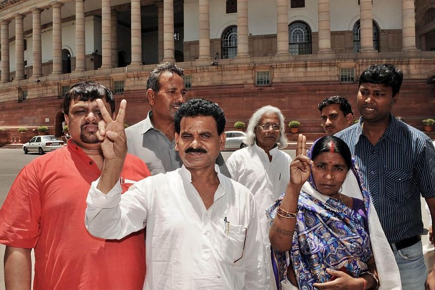 The first elected Maoist politician to the Indian Parliament Kameshwar Baitha (centre) gestures as he poses with supporters at Parliament House in New Delhi, June 8, 2009. The list of charges against Indian politician Kameshwar Baitha is long and sta