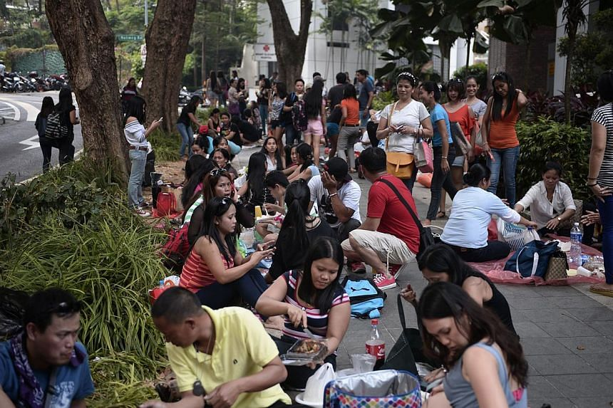 A crowd mostly having picnics in their own groups opposite Lucky Plaza at Tong Building, on March 9, 2014. Just over a third of more than 2,000 maids who started working in Singapore last year received a weekly rest day, the Manpower Ministry (M
