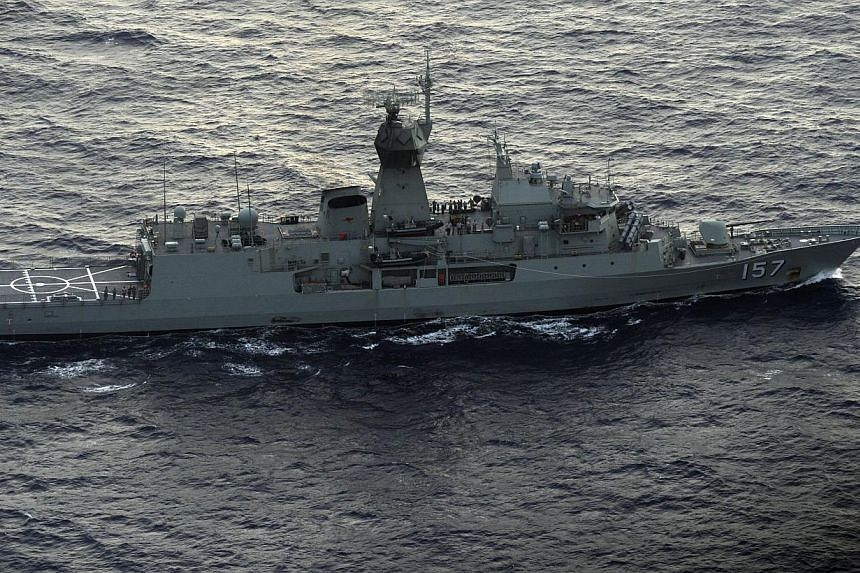 In this photo taken from a Royal New Zealand Airforce P-3K2-Orion aircraft, the Australian ship HMAS Perth is guided into position by the RNZAF aircraft to recover a red object during the search for missing Malaysia Airlines flight MH370, off Perth o