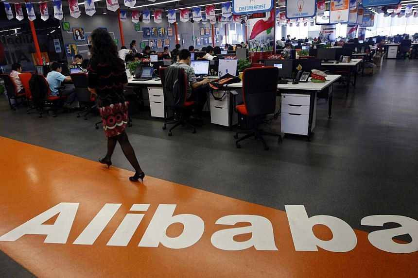 """An employee walks past a logo of Alibaba Group at its headquarters on the outskirts of Hangzhou, Zhejiang province.Global fund managers of nearly US$14 trillion (S$17.5 trillion) in assets support Hong Kong's """"one share, one vote"""" principle, an"""