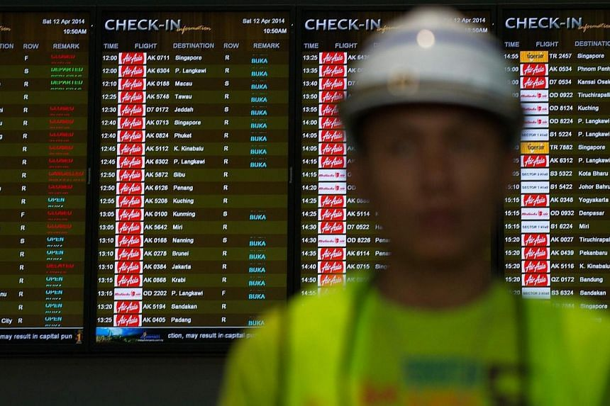 A worker walks in front of check-in time screens at the new low-cost airport at Kuala Lumpur International Airport 2 (KLIA2) in Sepang on April 12, 2014. Malaysian budget airline AirAsia said on Tuesday it would move to KLIA2 despite recently cr