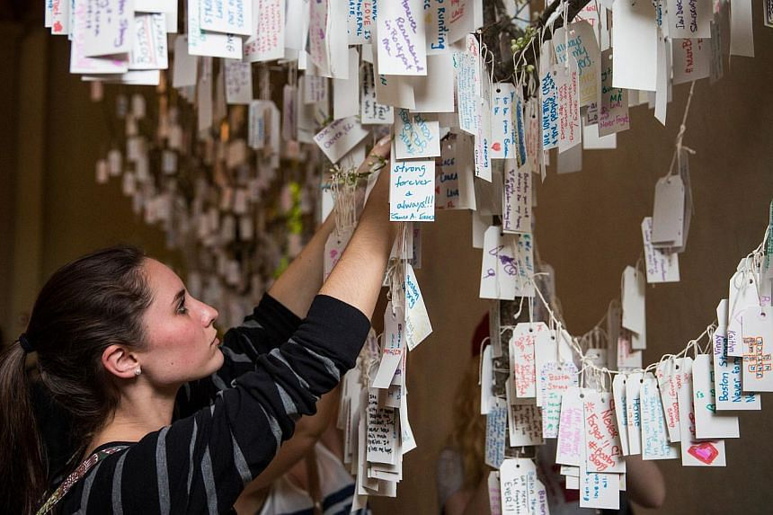 """Jillian Munson, from Rochester, New York, hangs a hand-written message she wrote on a tree hung with messages inside a display titled, """"Dear Boston: Messages from the Marathon Memorial"""" in the Boston Public Library to commemorate the 2013 Boston Mara"""