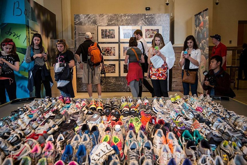 """Runner's shoes are laid out in a display titled, """"Dear Boston: Messages from the Marathon Memorial"""" in the Boston Public Library to commemorate the 2013 Boston Maraton bombings, on April 14, 2014 in Boston, Massachusetts. -- PHOTO: AFP"""