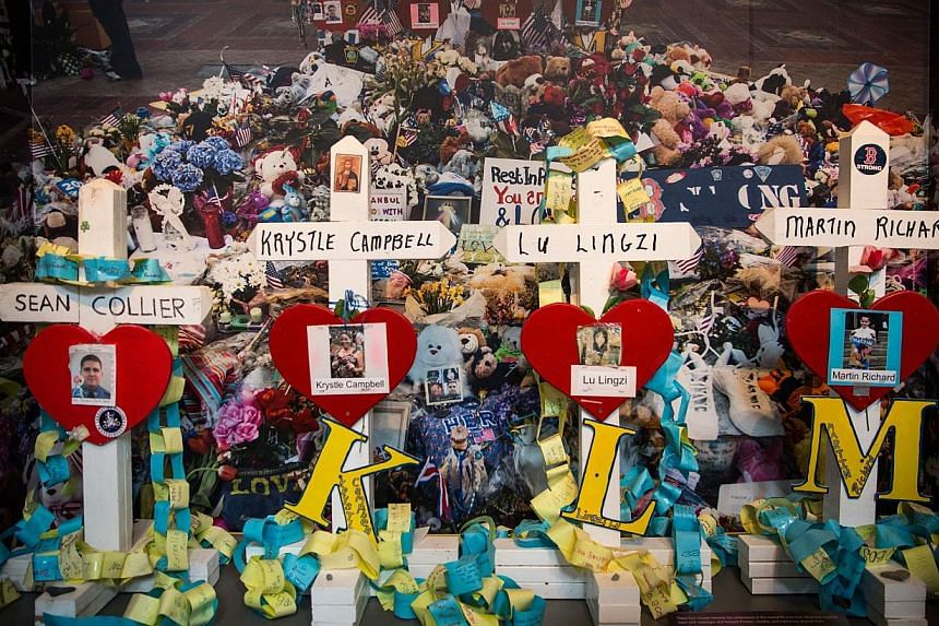 """Crosses bearing the names of people killed are displayed in an exhibit titled, """"Dear Boston: Messages from the Marathon Memorial"""" in the Boston Public Library to commemorate the 2013 Boston Maraton bombings, on April 14, 2014 in Boston, Massachusetts"""