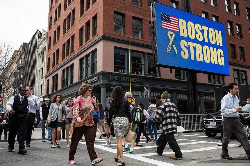 "People walk past an electronic billboard reading ""Boston Strong"" near the finish line of the Boston Marathon, on April 14, 2014 in Boston, Massachusetts. -- PHOTO: AFP"