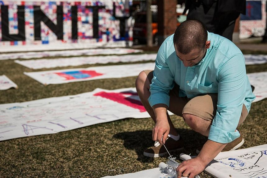Jamal Alkattan pins down a corner of a memorial quilt prior to a flag raising ceremony at Boston Medical Centre to commemorate the one year anniversary of the Boston marathon bombings on April 14, 2014 in Boston, Massachusetts. -- PHOTO: AFP