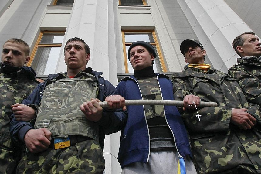 """Members of a """"Maidan"""" self-defence unit stand guard in front of the Ukrainian parliament building in Kiev on April 15, 2014.Russia declared Ukraine on the brink of civil war on Tuesday, April 15, 2014, as Kiev said an """"anti-terrorist operation"""""""