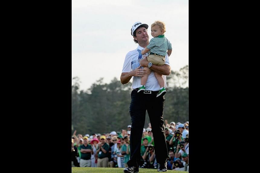 American Bubba Watson walking with his son Caleb off the 18th green on Sunday after winning the Masters by three strokes over Jonas Blixt and Jordan Spieth at Augusta National Golf Club.