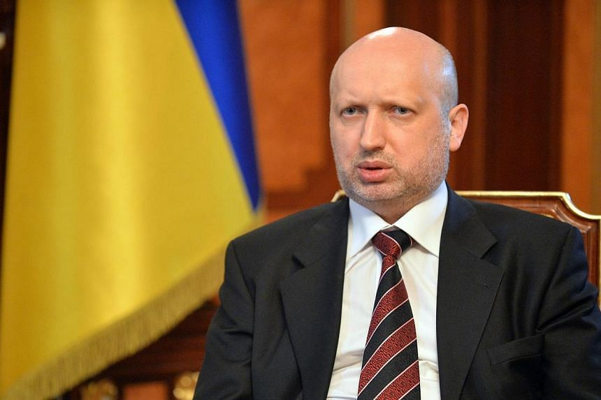 Olexander Turchynov, speaker of the Ukrainian parliament and interim Ukrainian president (center) answers questions during an exlusive interview in Kiev on March 11, 2014. Ukraine's acting president accused Russia on Tuesday, April 15, 2014, of