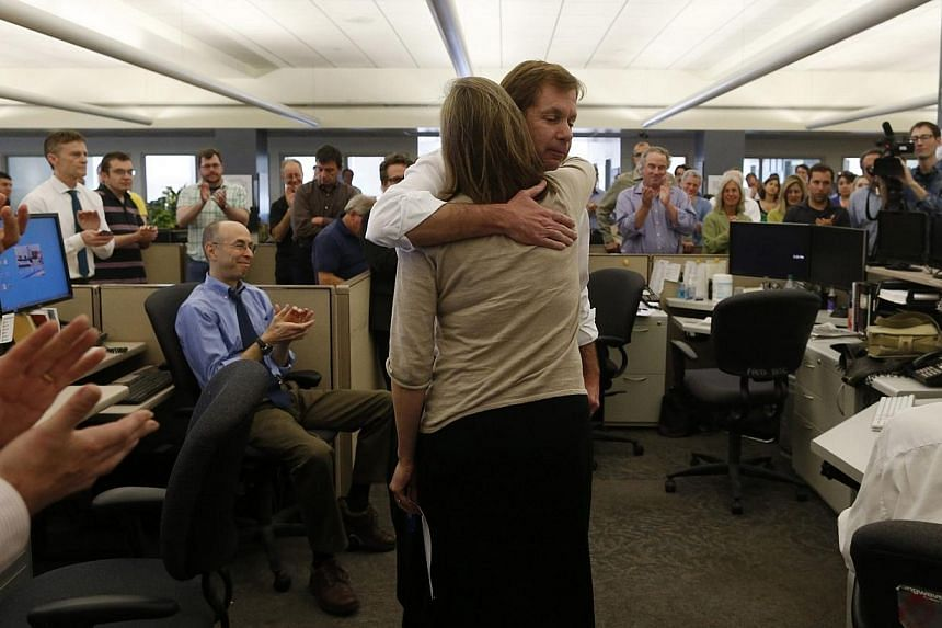 Editor Brian McGrory hugs Metro editor Jennifer Peter after the newspaper was awarded a Pulitzer Prize for breaking news in Dorchester, Massachusetts on April 14, 2014. -- PHOTO: REUTERS
