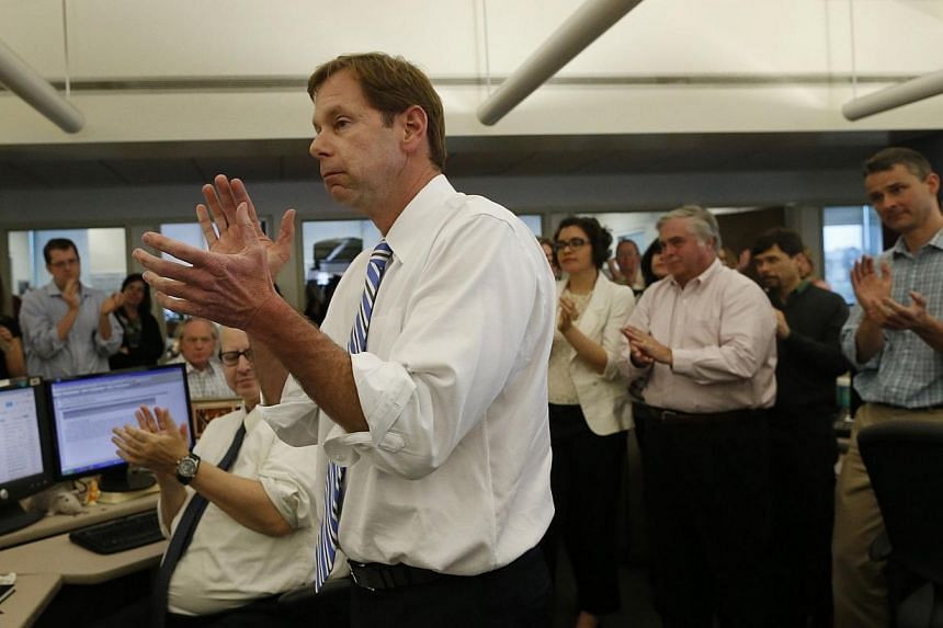 Editor Brian McGrory and members of the newsroom applaud after the newspaper was awarded a Pulitzer Prize for breaking news in Dorchester, Massachusetts on April 14, 2014. -- PHOTO: REUTERS