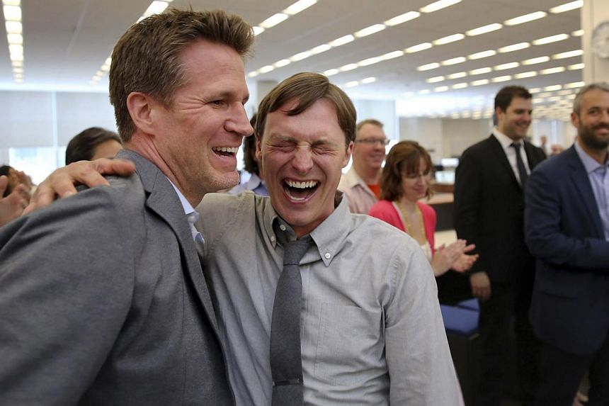 The New York Times photographer Josh Haner (centre) with sports editor Jason Stallman, after it was announced that Mr Haner won the Pulitzer prize in New York on April 14, 2014. -- PHOTO: REUTERS