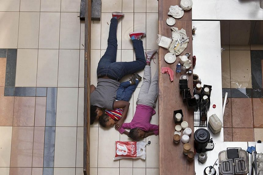 A woman and children hiding inside the Westgate Mall during an attack by militants in Nairobi, Kenya on Sept 21, 2013. -- FILE PHOTO: AFP