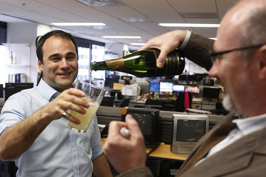 Reuters journalist Jason Szep (left) celebrates with colleague Alistair Bell in the Reuters Washington bureau after it was announced Mr Szep and a team from Reuters won a Pulitzer prize for international reporting on the violent persecution of a Musl
