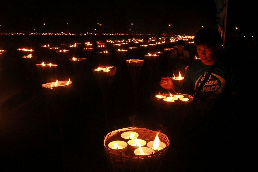 Participants stand next to lit candles in a bid to set a new world record for largest flaming image in Iloilo City, central Philippines on April 14, 2014. Hundreds of people lined up in a dark, muddy field to form a giant map of the Philippines in a