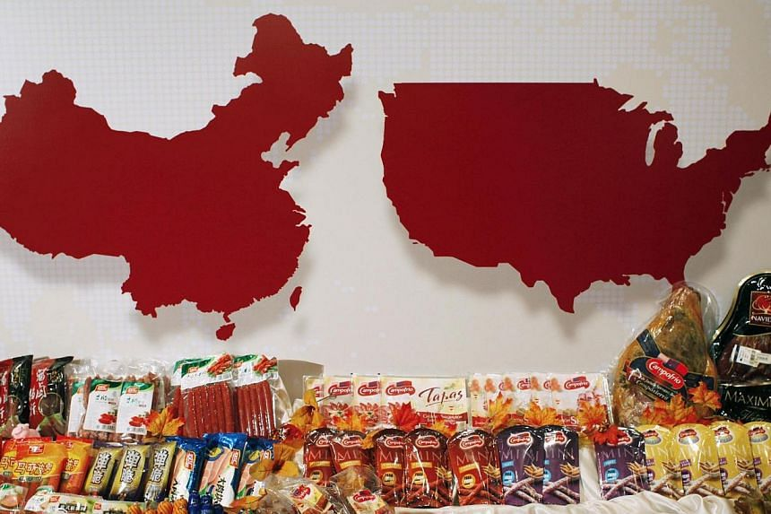 Some of the products of WH Group are displayed in front of maps of Europe and China at a news conference on the company's IPO in Hong Kong on April 14, 2014. Chinese pork producer WH Group has issued shares worth US$597 million (S$747 million) t