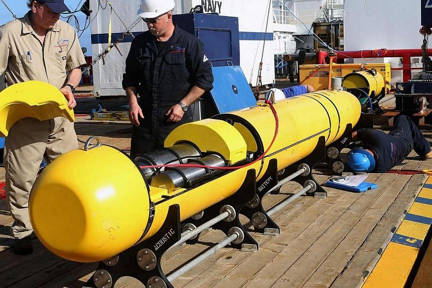 Phoenix International workers Chris Minor (right) and Curt Newport inspect the US Navy's Bluefin 21 autonomous underwater vehicle (AUV) before deployment in the southern Indian Ocean to look for the missing Malaysia Airlines flight MH370 in this ha