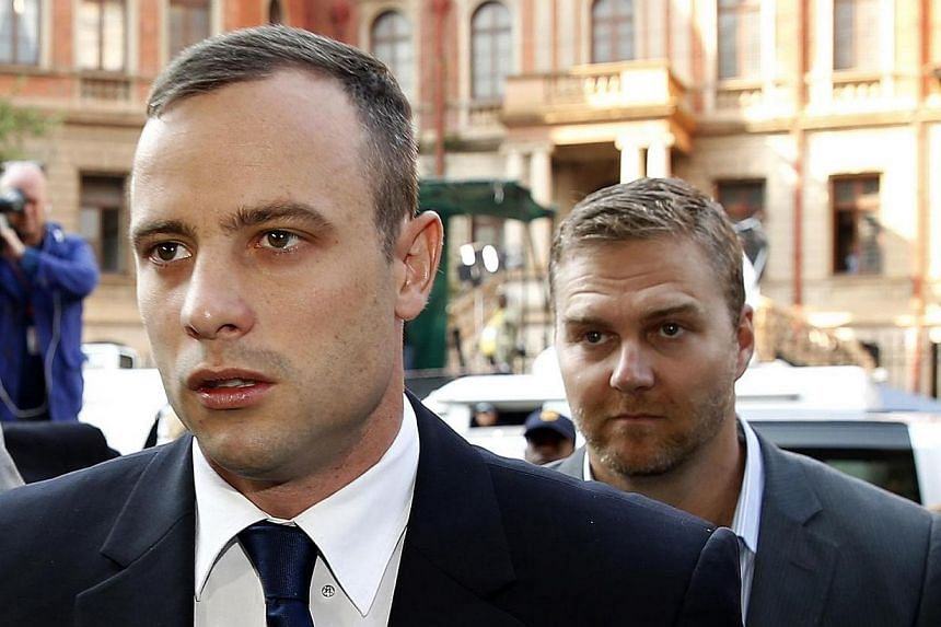 Olympic and Paralympic track star Oscar Pistorius (left) arrives ahead of his trial at North Gauteng High Court in Pretoria on Tuesday, April 15, 2014. South African prosecutor Gerrie Nel indicated on Tuesday that he would wrap up his searing cr