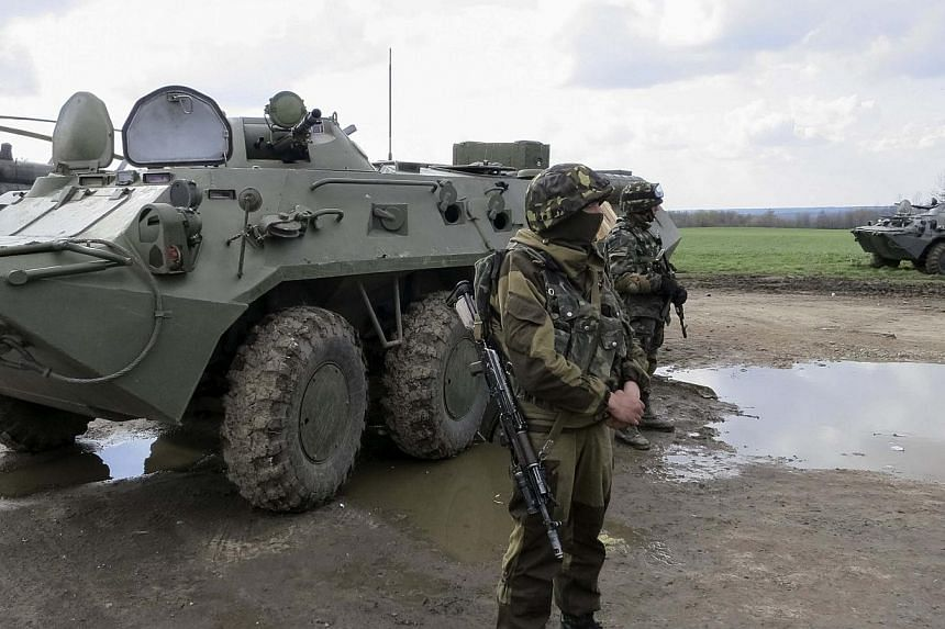 "Ukrainian soldiers are seen near armoured personnel carriers at a checkpoint near the town of Izium in eastern Ukraine on Tuesday, April 15, 2014. Ukrainian armed forces on Tuesday launched a ""special operation"" against separatists in the town o"