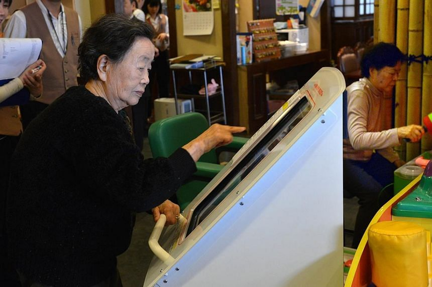 An elderly woman plays a game at a nursing home in Yokohama on Feb 7, 2014. Japan's population has shrunk for the third year running, with the elderly making up a quarter of the total for the first time, government data showed on Tuesday. -- FIL