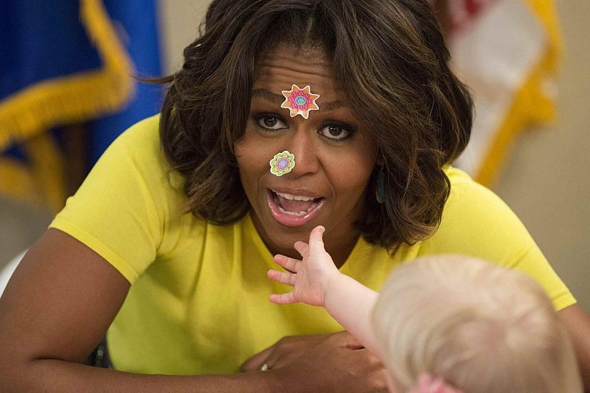 United States First Lady Michelle Obama has stickers put on her face by 20-month-old Lily Oppelt during a visit with children at the Fisher House at Walter Reed National Military Medical Centre in Bethesda, Maryland on April 14, 2014. -- PHOTO: REUTE