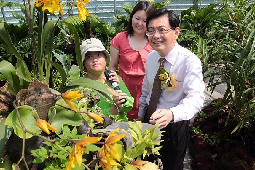 Minister for Education Mr Heng Swee Keat (right) is shown the flowers and plants in D'Amozon Rainforest by Delta Senior School student Ms Nina Sarah Faizah (in green) during a tour of the school's facilities.-- ST PHOTO: NEO XIAOBIN