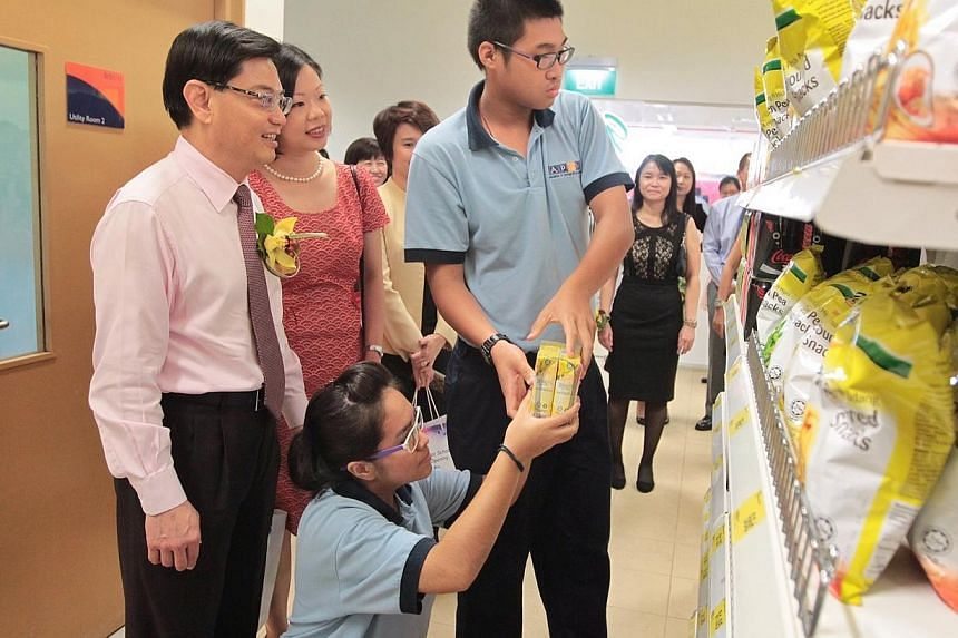 Minister for Education Mr Heng Swee Keat (extreme left) and Minister of State for Education Ms Sim Ann (in red), watch as Delta Senior School students Ms Nuramalina (third from left) and Mr Alvin Lai (centre) arrange drink packets on the shelves at t