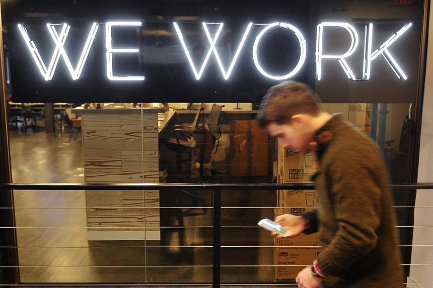 """A man walks past the neon sign in front of the """"We Work"""" co-operative co-working space on March 13, 2013 in Washington, DC. -- FILE PHOTO: AFP"""