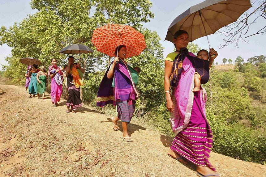 Women carrying their children walk back to their homes after casting their vote at a polling station at Putsari village in the north-eastern Indian state of Assam on April 12, 2014. -- FILE PHOTO: REUTERS