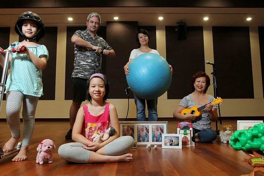 Paul Rae and Kaylene Tan (fourth from left) with daughters Summer (left) and Lola, and Eleanor Song, Tan's mother, in Family Duet. -- PHOTO: ST FILE